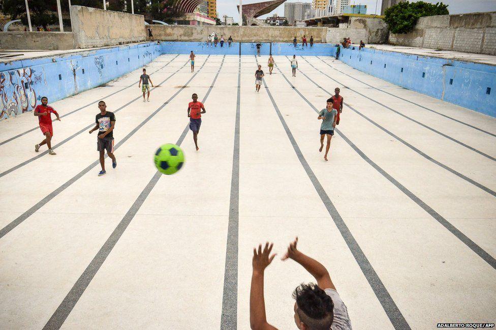 Cubans play football in an empty pool in Havana