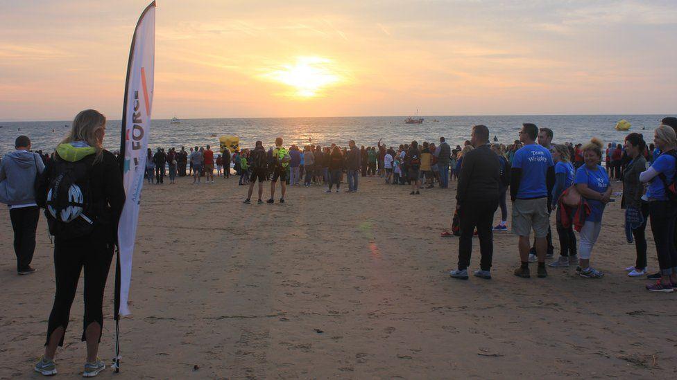 Wrth i'r nofwyr bellhau ar y gorwel, mae'r haul yn codi // As the swimmers start to disapear on the horizon, the sun makes an appearance