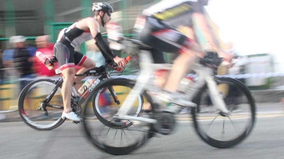 Mae pob eiliad yn cyfri mewn rhas secilo 180km // Every second counts on the 180km bike ride