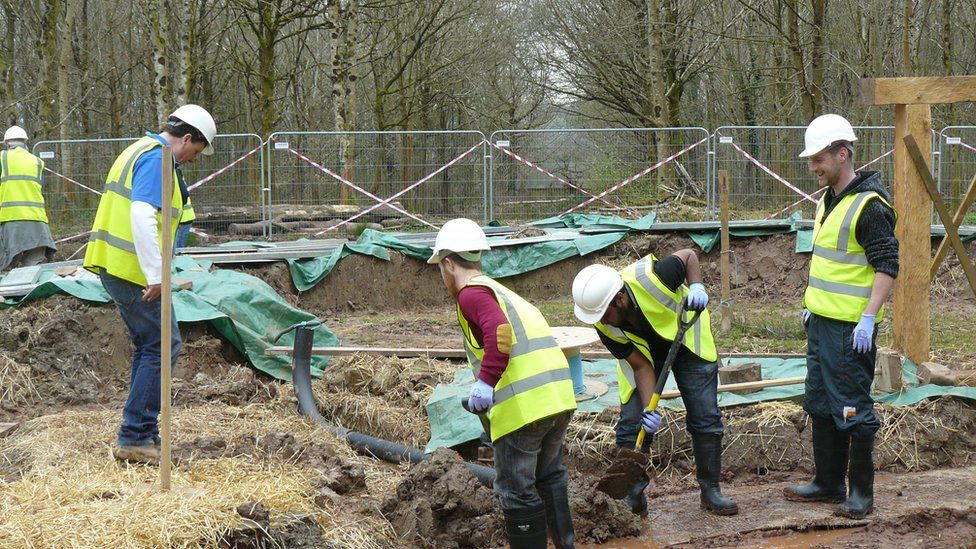 Gwirfoddolwyr yn helpu i godi'r waliau // Volunteers helping to build the walls