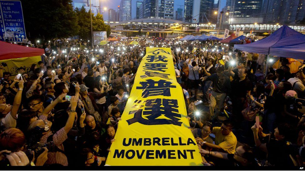 """Pro-democracy protesters spread a yellow banner with the words reading: """"I want genuine universal suffrage"""" at a rally in the occupied areas outside government headquarters in Hong Kong""""s Admiralty Tuesday, 28 Oct 2014."""