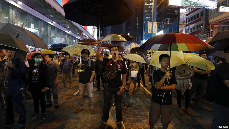 Pro-democracy protesters hold up umbrellas and chant slogans to mark the one-month anniversary of the Occupy civil disobedience movement as they block a main road at Mongkok shopping district in Hong Kong 28 October 2014