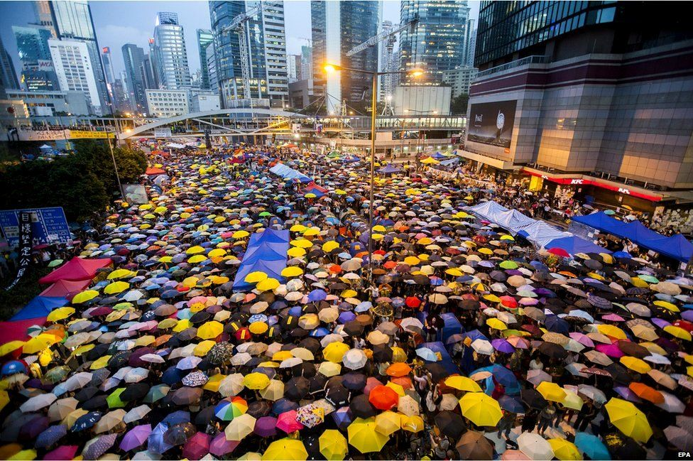"""Pro-democracy protesters open their umbrellas for 87 seconds, marking the 87 rounds of tear gas that were fired by the Hong Kong police at unarmed student protesters in exactly the same location one month ago, at the Admiralty protest zone which has been newly dubbed """"Umbrella Square"""", Admiralty, Hong Kong, China, 28 October 2014"""
