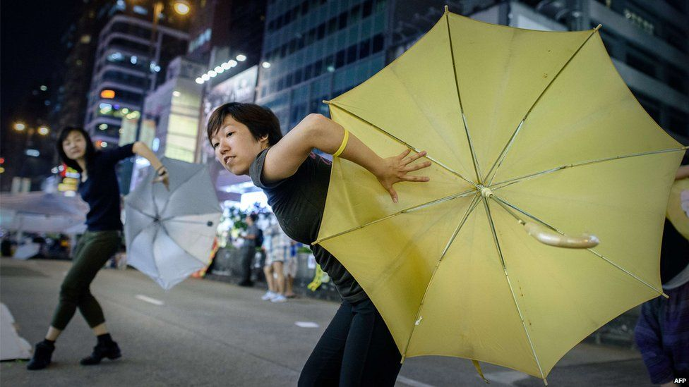 Pro-democracy protesters dance with umbrellas to mark one month since they took to the streets, in the Mongkok district of Hong Kong on 28 October 2014