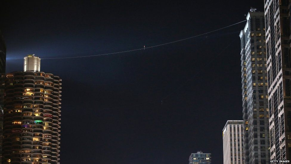 Nik Wallenda walks on a wire from Chicago's Marina City's tower to Leo Burnett building