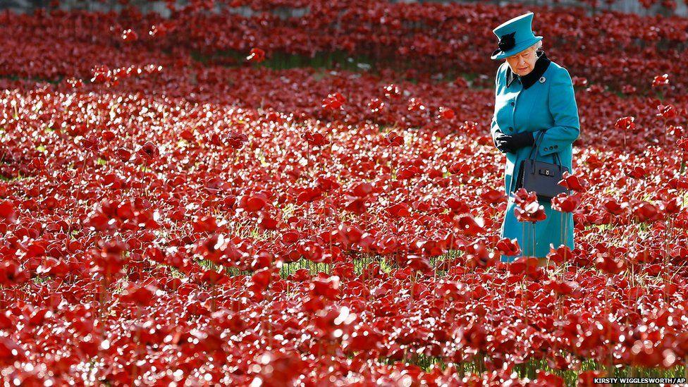 Britain's Queen Elizabeth II walks through a field of ceramic poppies