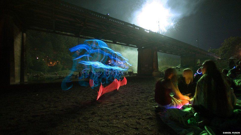 Man selling glow sticks at night