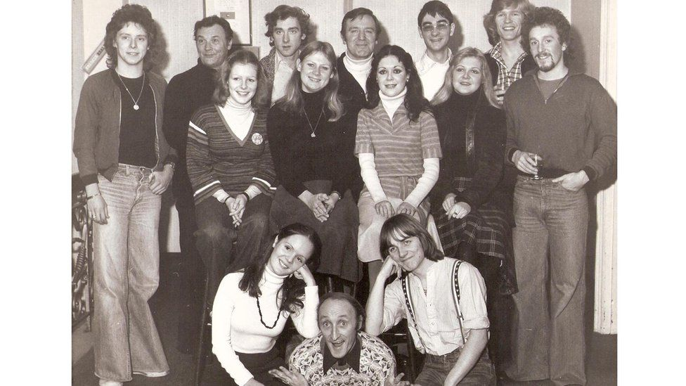 Ryan gydag aelodau cast Babes in The Wood yn 1977. Wythnosau wedi tynnu'r llun hwn, roedd wedi marw // Ryan backstage with the cast of Babes in The Wood in 1977. Some weeks after this picture was taken, Ryan was dead