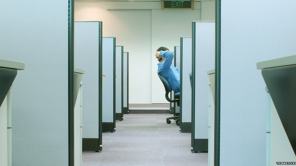 Man leans back in cubicle