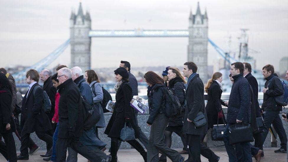 Commuters walking over London Bridge