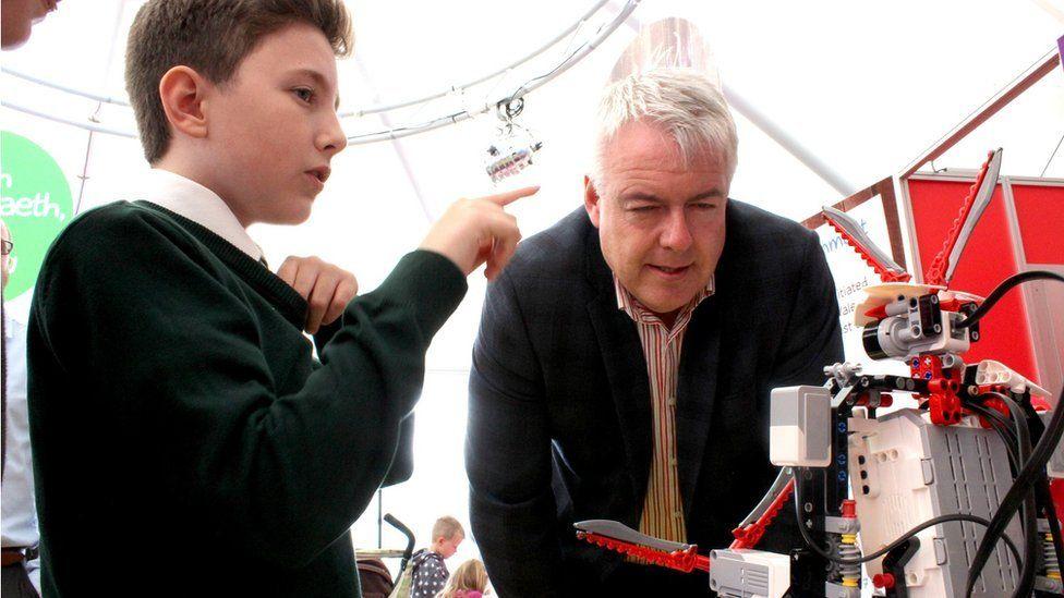 Y Prif Weinidog, Carwyn Jones, yn cwrdd ac un o etholwyr y dyfodol? // First Minister Carwyn Jones ponders whether robots will have the vote in the future
