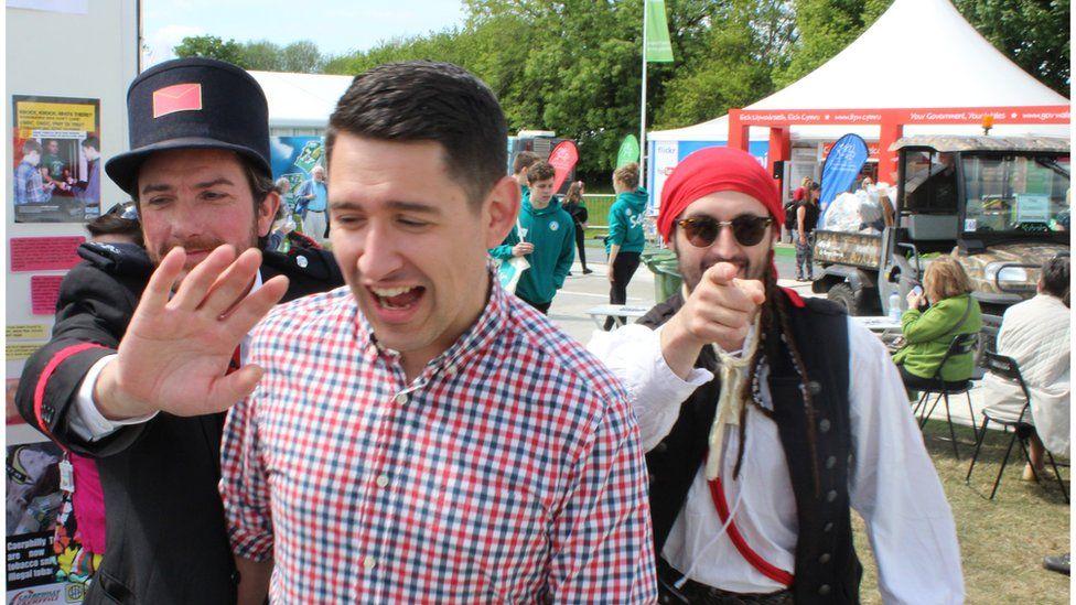 Gareth Delve, cyflwynydd Cyw yn cael ei dywys ar hyd y maes gan ei warchodwyr // S4C's Cyw presenter, Gareth Delve, being guided around the Maes by his entourage!