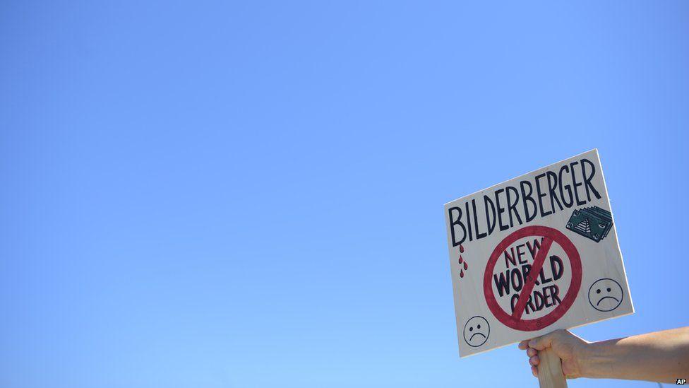 """A placard reads """"bilderberger new world order"""""""