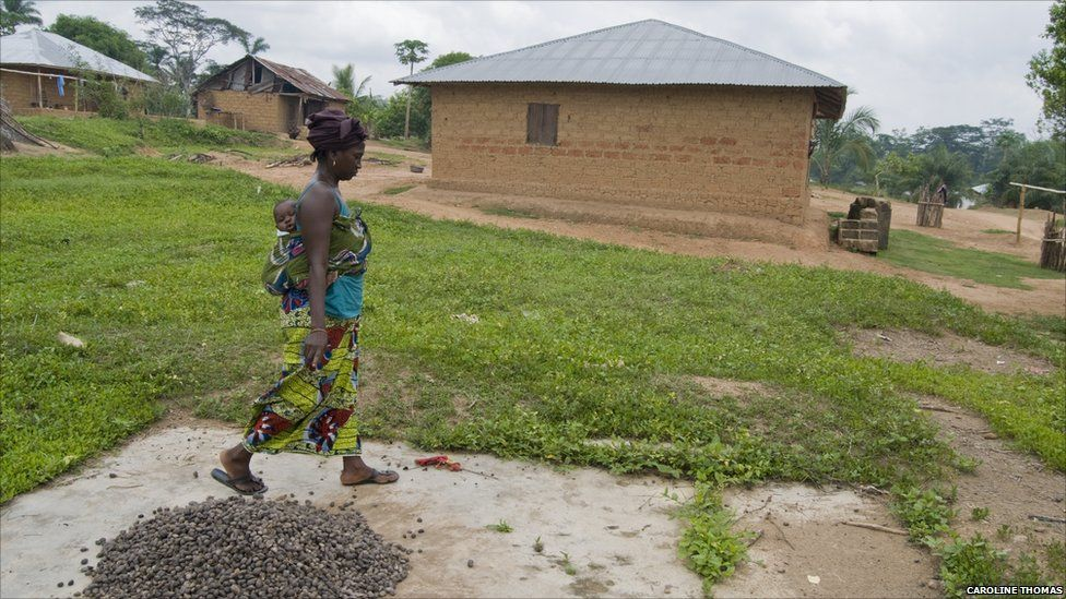 Mama Torma walks on what is left of her old home in the village of Mandopohlun