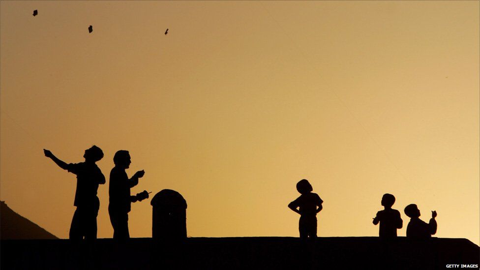 Boys fly kites at sunset on a Kabul rooftop.