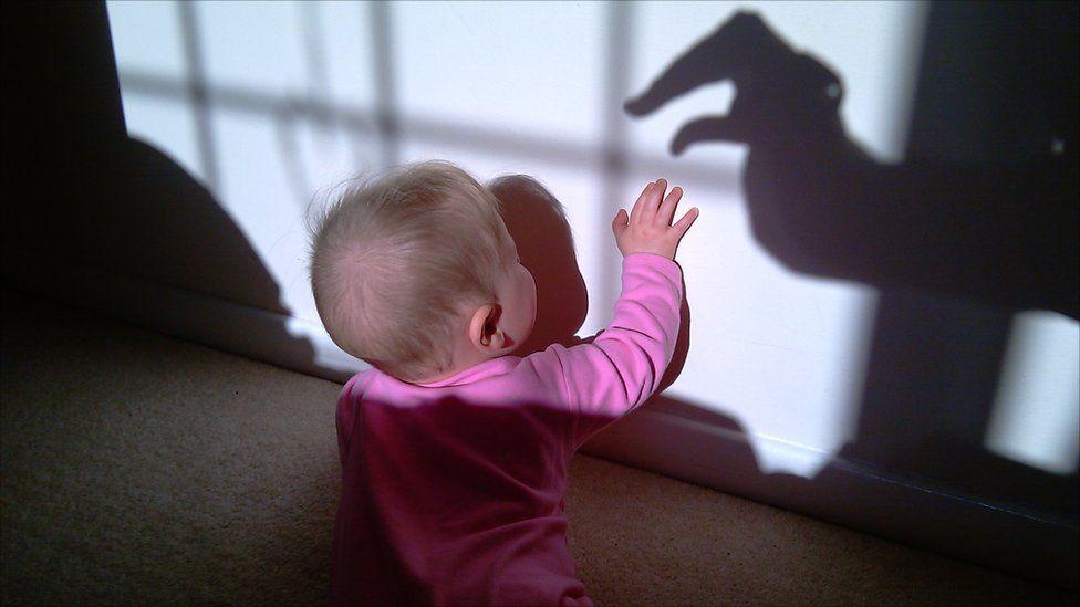 A baby tries to touch a shadow of a hand