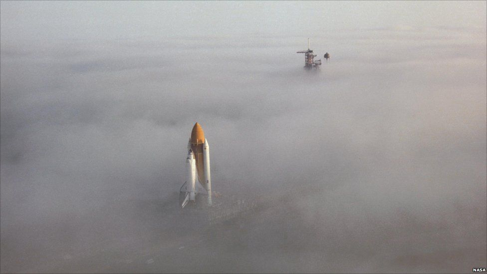 Space Shuttle Challenger moves through the fog on its way down the crawler way en route to Launch Pad 39A at Kennedy Space Center