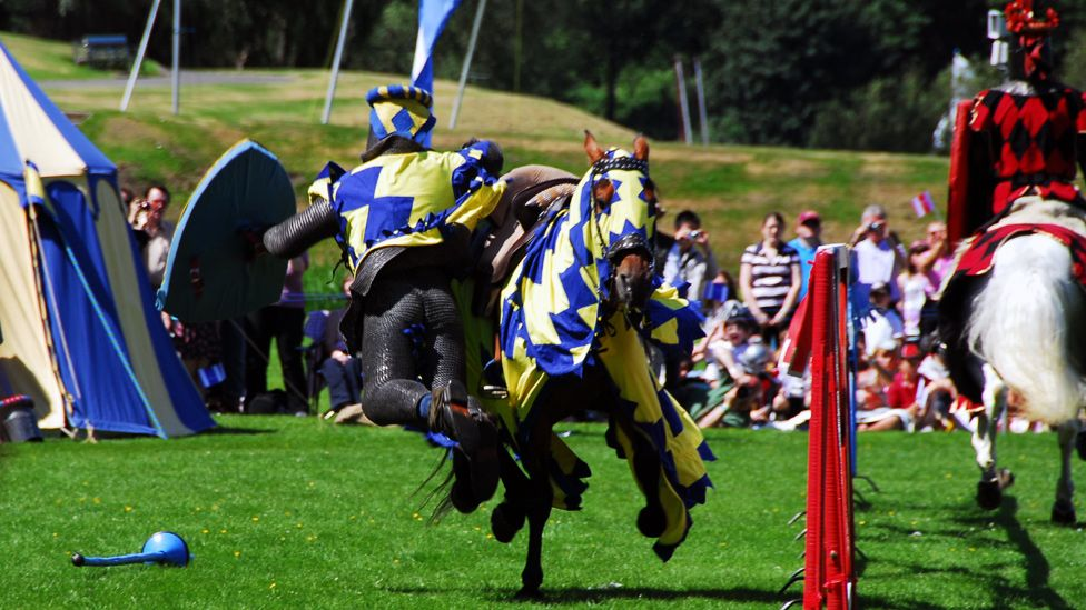 A knight falls from his horse during a jousting event