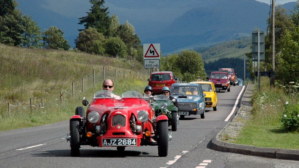 Line of three-wheeled cars on a road