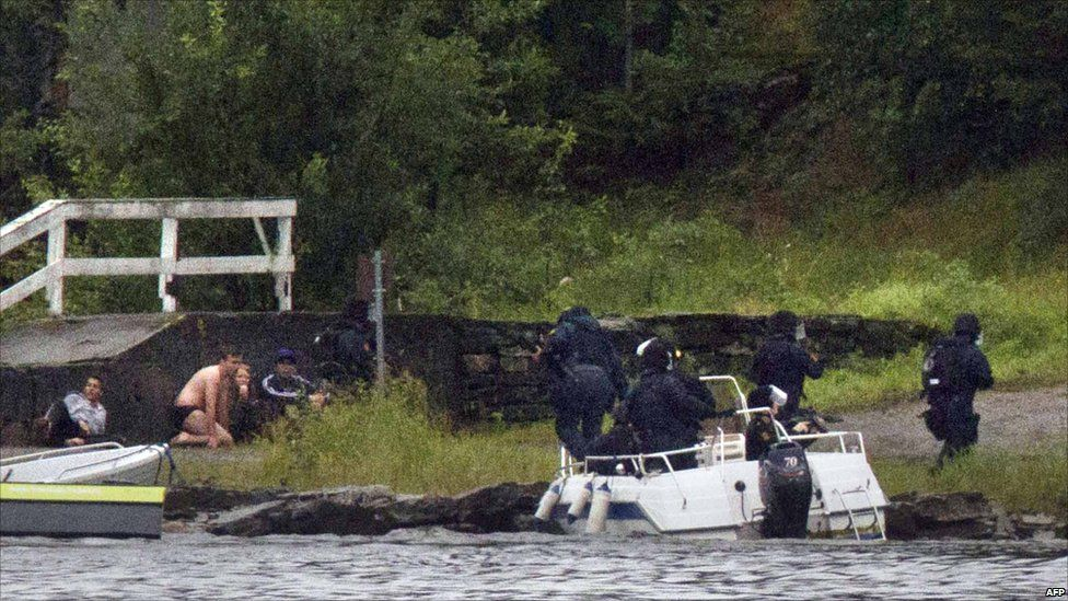 Armed police aim their weapons while people take cover after the shootings on Utoya island, some 40km south-west of Oslo, 22 July 2011