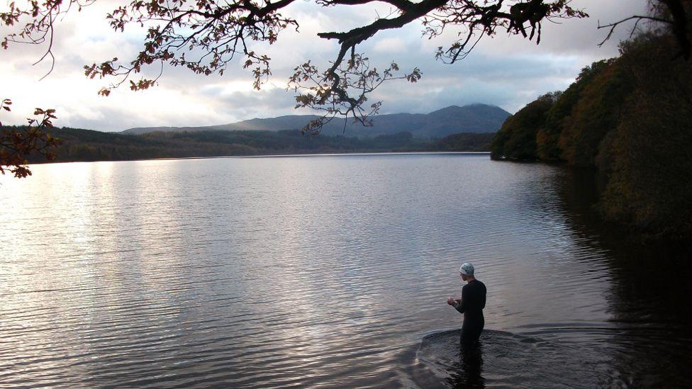 Man standing in Loch Venachar