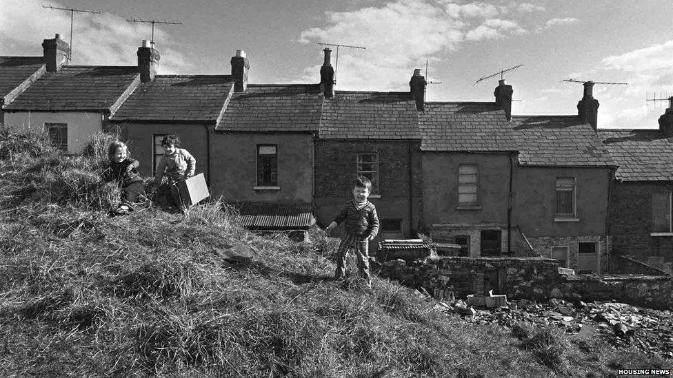 Children play behind homes in Ligoniel in 1975