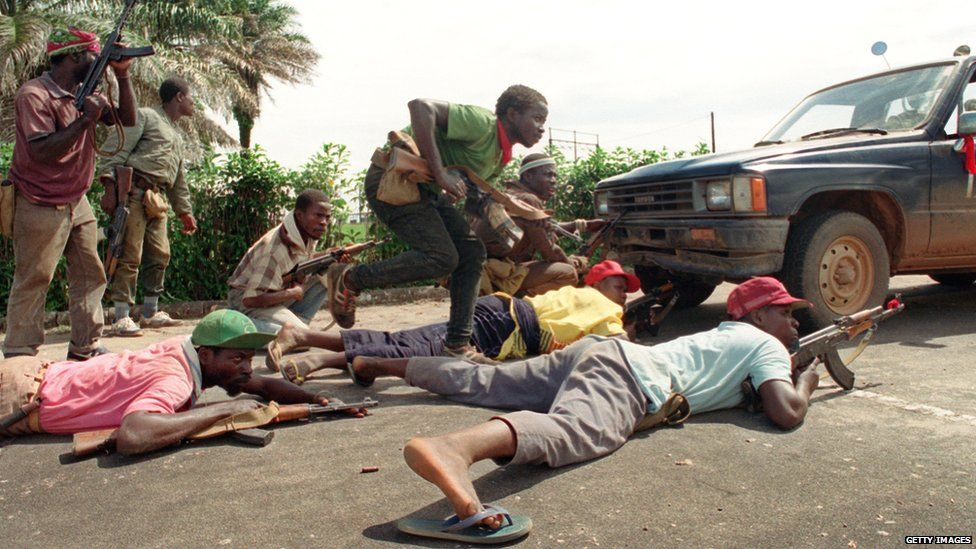 Rebels loyal to Charles Taylor of the National Patriotic Front of Liberia (NPFL) take position behind a truck 30 May 1990 in Monrovia during heavy clashes with the Armed Forces of Liberia (AFL) loyal to president Doe.