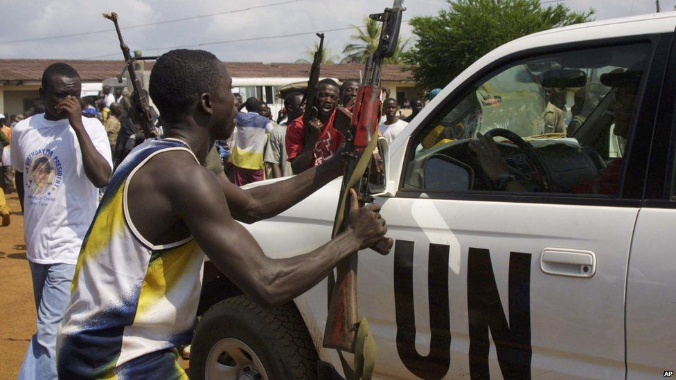 A fighter loyal to Charles Taylor tries to surrender arms to UN soldiers at Campe Schieffelin outside Monrovia, 7 September 2003