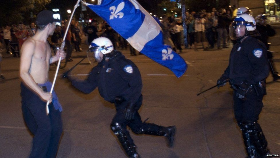 Policeman charges at a man protesting tuition fee increases Montreal, Canada 23 May 2012
