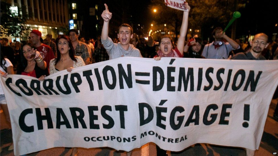 Protesters walk with a large banner in demonstrations against rising tuition fees in Montreal, Canada 23 May 2012