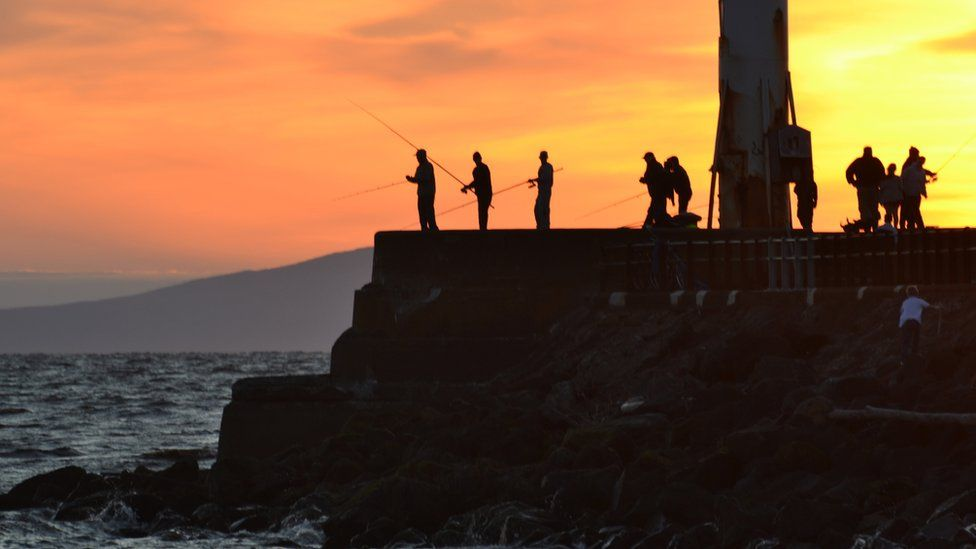 Fishermen on the pier at sunset