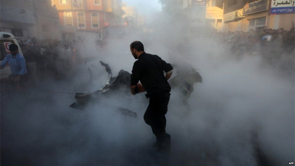 Palestinian firefighters extinguish the blaze on the burning wreckage.