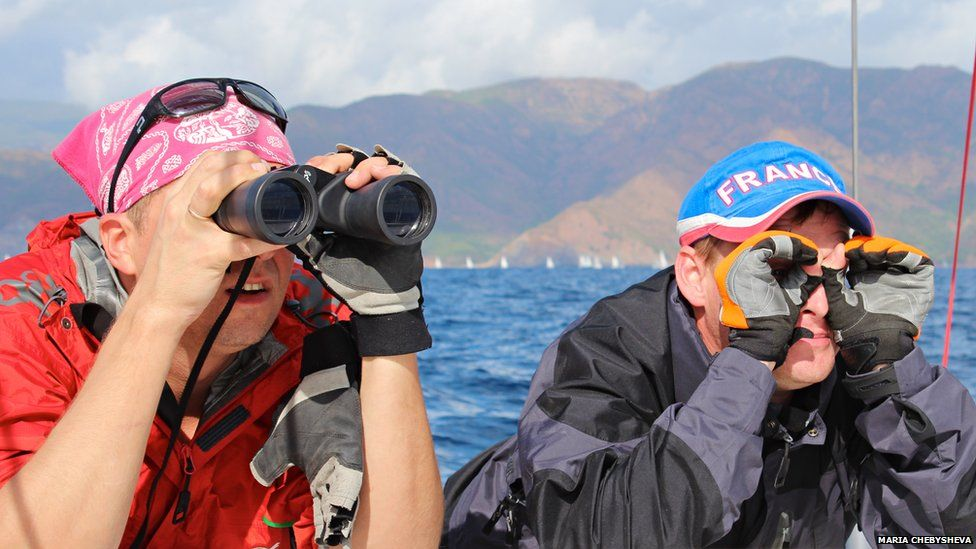 Two people, one using binoculars, the other pretending to