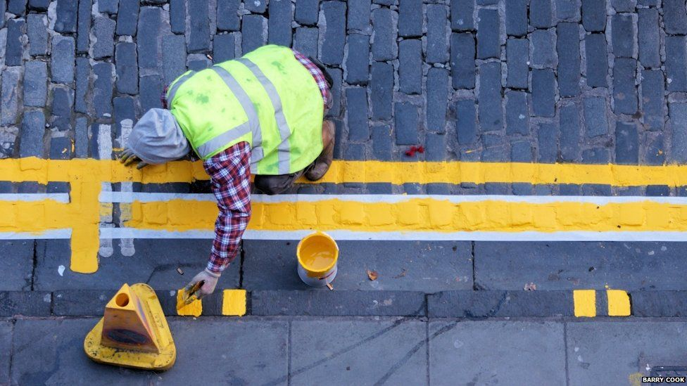 Workman painting yellow lines