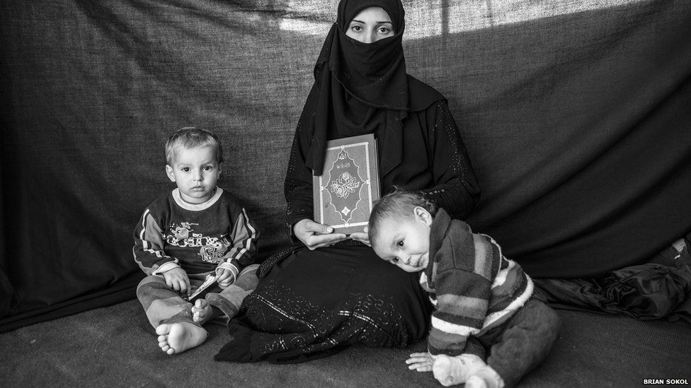 Syrian refugee Iman sits with her children Ahmed and Aisha, while holding a copy of the Koran.