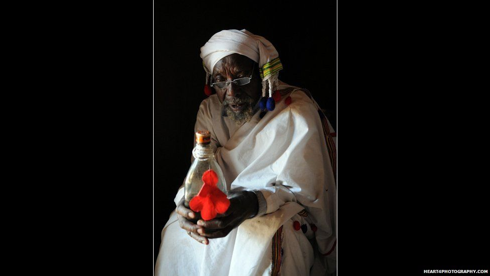 A traditional healer in southern Tanzania holding a bottle