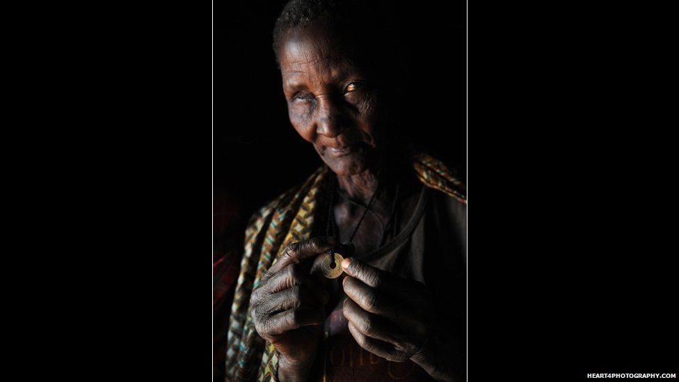 Wife of traditional healer in southern Tanzania holding a coin