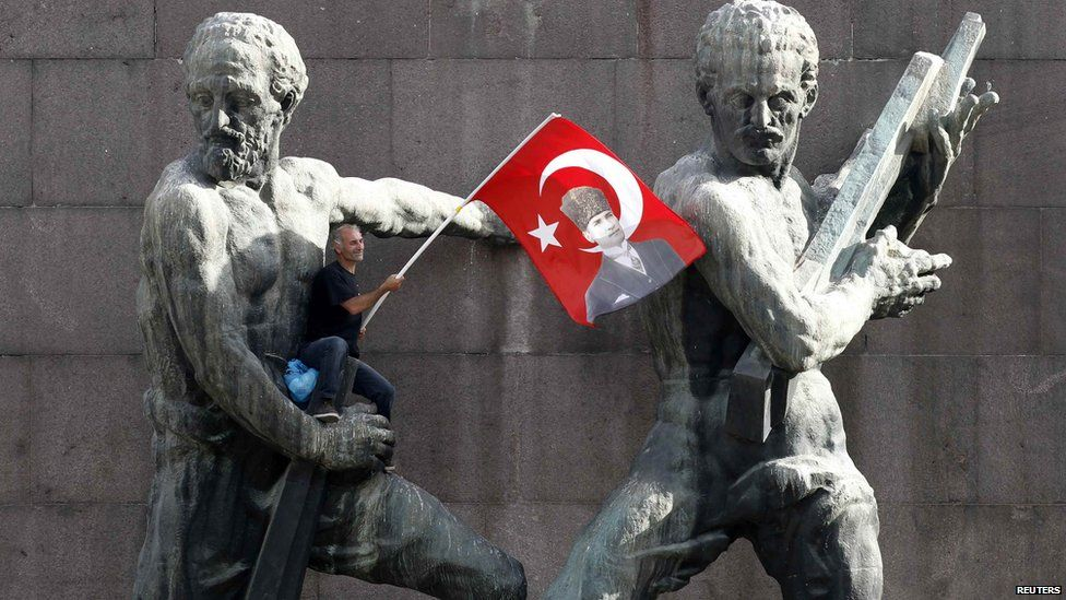 A demonstrator waves Turkey's national flag as he sits on a monument during a protest in central Ankara, 2 June.