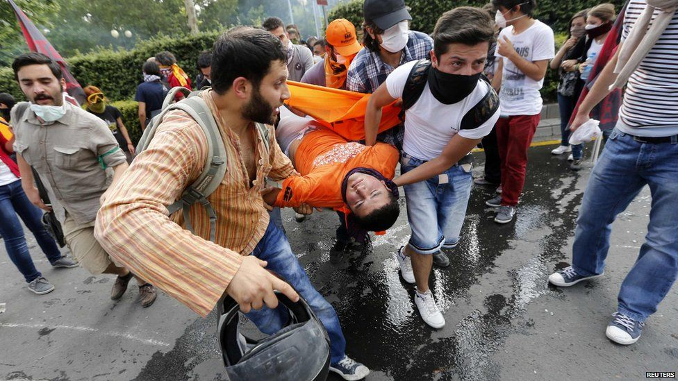 Protesters carry an injured man in central Ankara, 2 June.