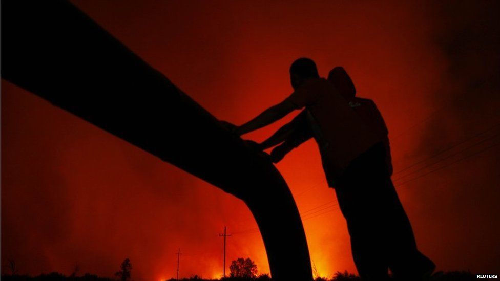 Villagers standing beside on an oil pipe are silhouetted by flames burning a palm-oil plantation in Bangko Pusako district, Riau province, June 22