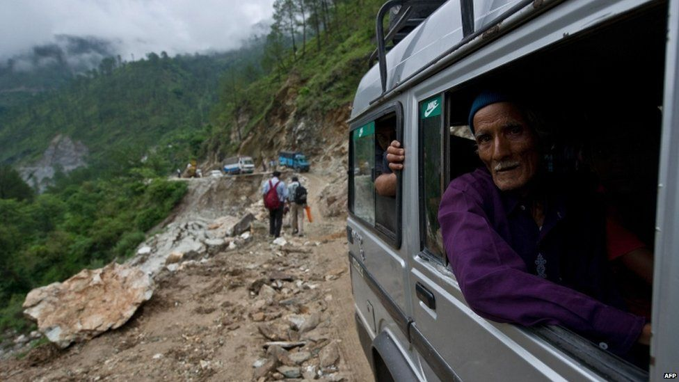 A man looks out as he drives past a damaged section of road between the town of Rudraprayag and Gauchar, Uttarakhand