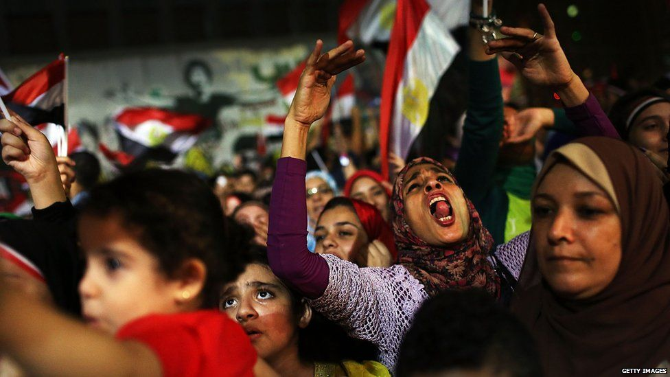 Egyptian women and children gather in the street as part of celebrations following the ousting of President Mohammed Morsi