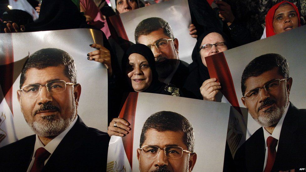 Supporters of ousted Egyptian president Mohammed Morsi hold his portrait during a rally outside Rabaa al-Adawyia mosque in Cairo