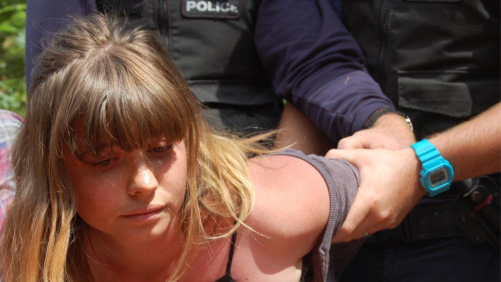 Woman having her arm held by police officer