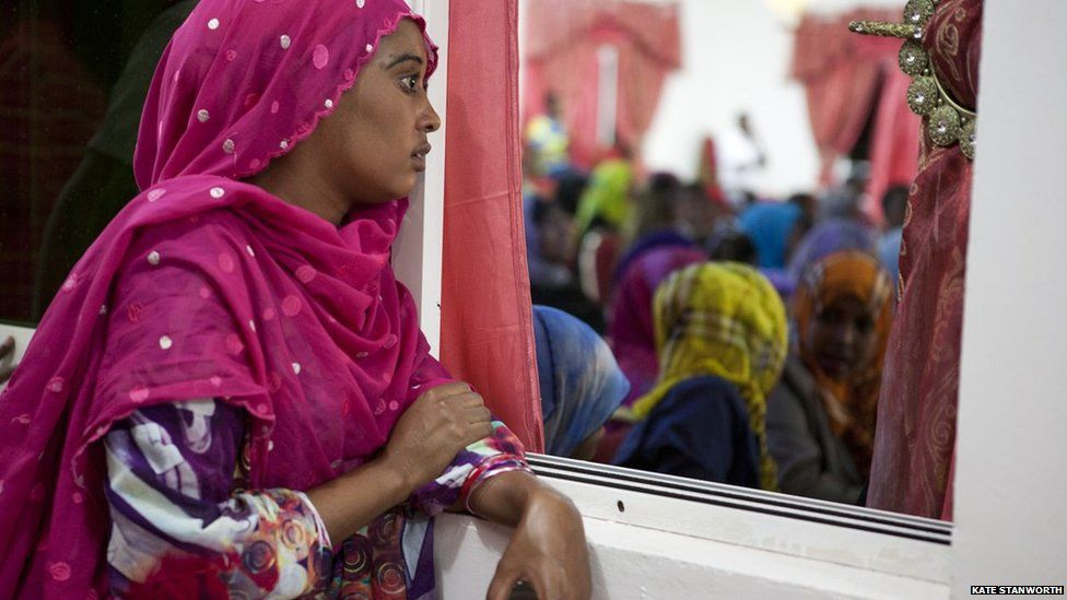 A woman watches through a window as a play is being performed, addressing the theme of corruption, during the closing ceremony of the book fair, in front of a diverse crowd of guests including government ministers and elders- Hargeisa, Somaliland