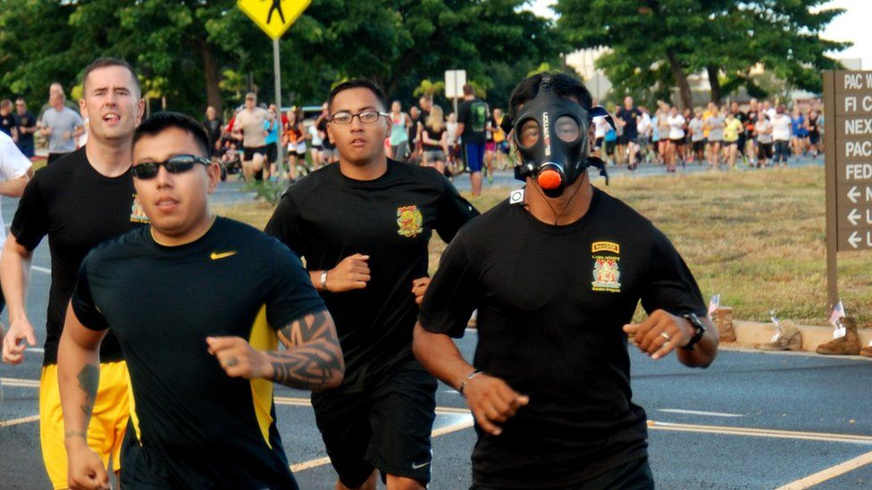 Runners in black attire, including one man in a gas mask.