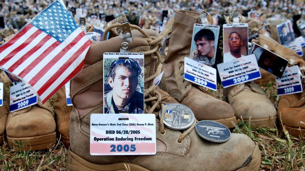Boots with photos, flags and medals attached to them