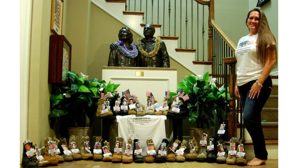 Theresa Johnson poses with a selection of boots with flags and photos attached