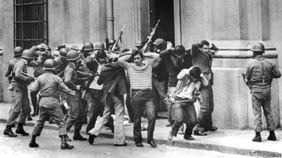 Aides and members of the presidency of former Socialist President Salvador Allende being guarded by soldiers outside La Moneda presidential palace in Santiago