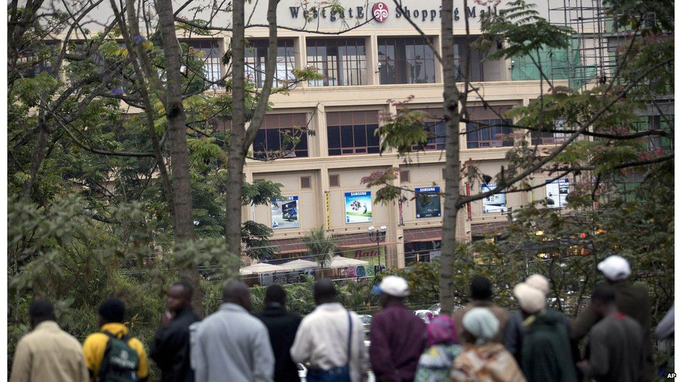 Onlookers gather on a hill to observe the Westgate Mall after a bout of heavy gunfire just after dawn in Nairobi, Kenya (23 Sept. 2013)